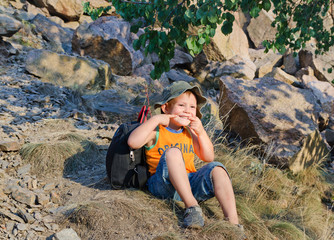 Cute little boy sitting on a mountain slope