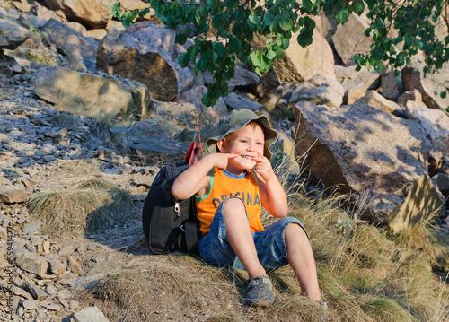 Cute little boy sitting on a mountain slope