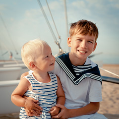 Portrait of young sailor and girl near yacht