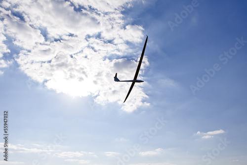 Glider keeping water on the background of the setting sun
