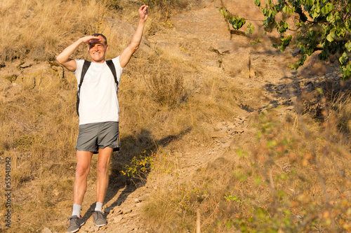 Backpacker waving on a mountains slope