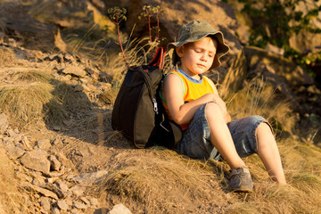 Little boy relaxing during a hiking expedition