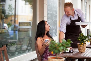 Schöne Frau im Straßencafe lächelt Kellner an