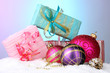 beautiful Christmas balls and gifts on snow on bright