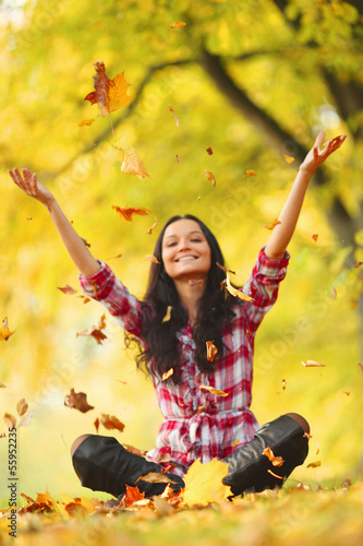 woman drop leaves in autumn park