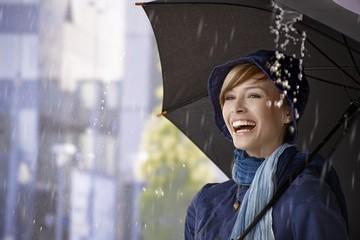 Happy young woman under umbrella in rain
