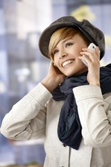 Outdoor portrait of young woman talking on mobile
