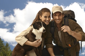 Portrait of young trekker couple with dog