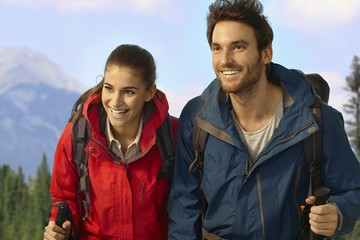 Trekking couple climbing uphill smiling.