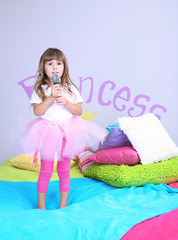 Little girl sings on bed in room on grey wall background