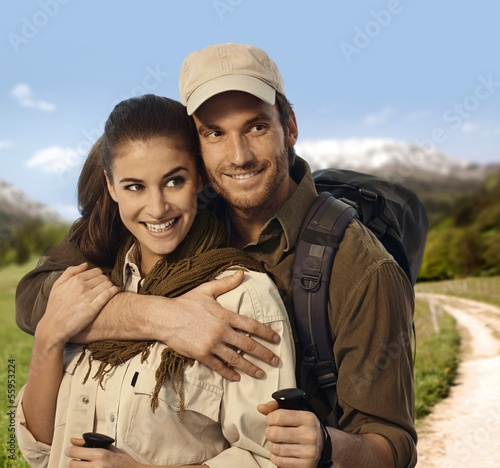 Hiking couple embracing in countryside