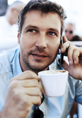 Young businessman talking on the phone and drinking coffee