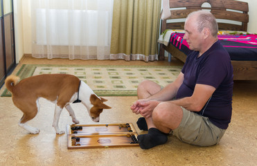 Young dog and mature man playing backgammon