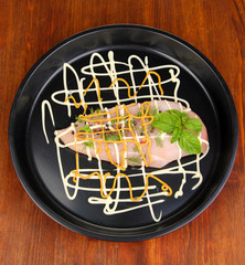 Raw chicken fillets on dripping pan, on wooden background