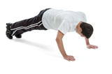 Teen boy doing push ups isolated on white