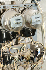 Two old, dirty meters for electricity with lot of wires