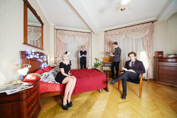 Young stylish people in retro room. Woman sits on bed