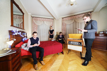 Young stylish people in retro room. Man sits on bed