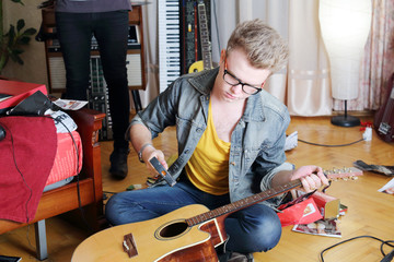 Young stylish man in glasses sits on floor and breaks guitar