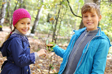 Boy in blue jacket holding green leaf and toadstool and girl