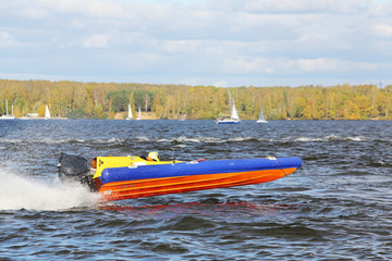 Sportsman fast  at power boat on river at competitions in fall.