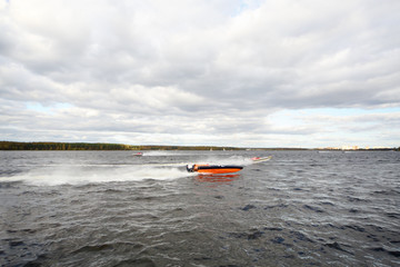 Many sportsmans fast float at motor boat on river at competition