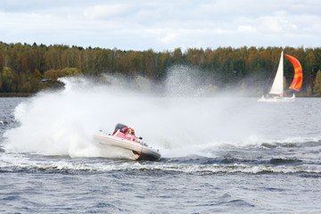 Man fast floats at power boat on river at competitions at autumn