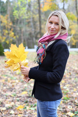 Happy blonde woman in black jacket with yellow in autumn forest.