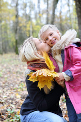 Happy blonde mother kisses her daughter with maple leaflets