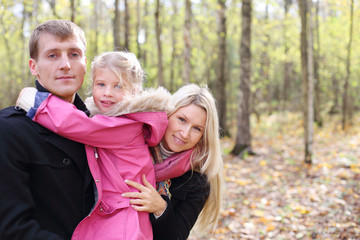 Happy daughter hugs father, and mother peeks out from behind