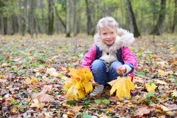 Little smiling girl squats and holds maple leaflets