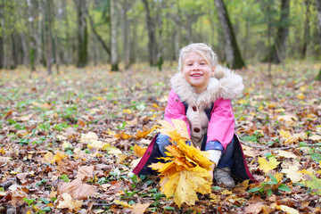 Little smiling girl squats with yellow maple leaflets and looks