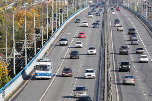 Many modern cars go on bridge at sunny day in Moscow, Russia.