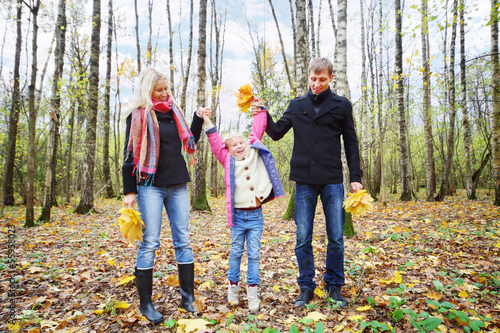 Happy father and mother with yellow maple leaves lift daughter