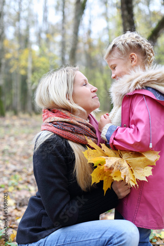 Happy blonde mother with maple leaflets looks at daughter