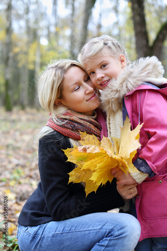 Happy mother with yellow maple leaflets hugs her daughter