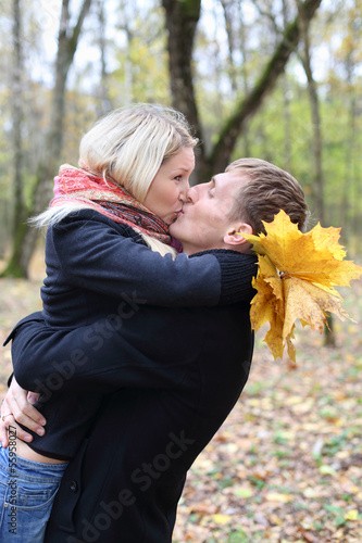 Husband and wife embrace and kiss in autumn forest