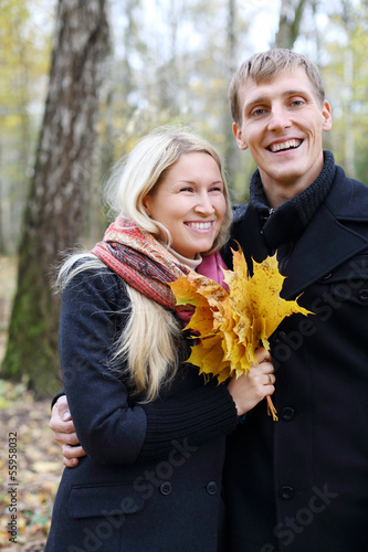 Happy husband and wife with yellow maple leafle laugh in autumn
