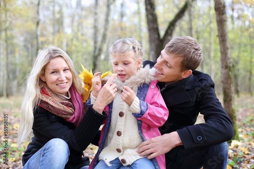 Happy father, mother and daughter with yellow maple leaves