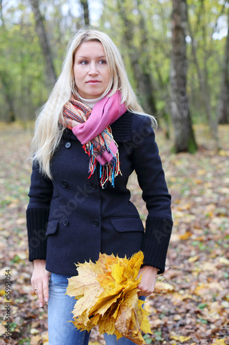 Sad beautiful woman with yellow maple leaflets