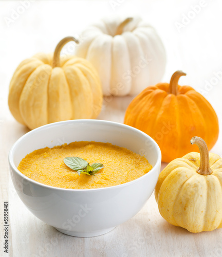 Pumpkin porridge and pumpkins on white wooden table