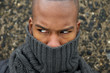 Black male fashion model with gray scarf covering face
