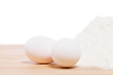 nahaufnahme von weissen eiern neben mehl