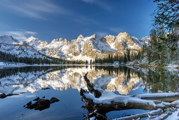 Winter mountain lake with log and reflections