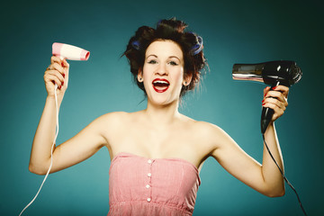 Funny girl in curlers with hairdryer styling hair