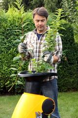 Gärtner steckt Äste in Schredderer, Handschuhe