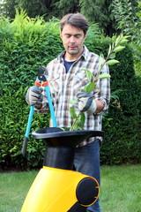 Gärtner mit Astsschere schreddert