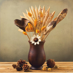 Dried flowers in wooden vase with pine corn