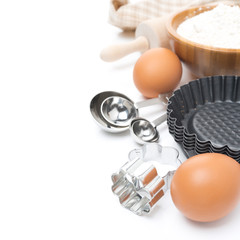 cookie cutters, measuring spoons, eggs and flour for baking