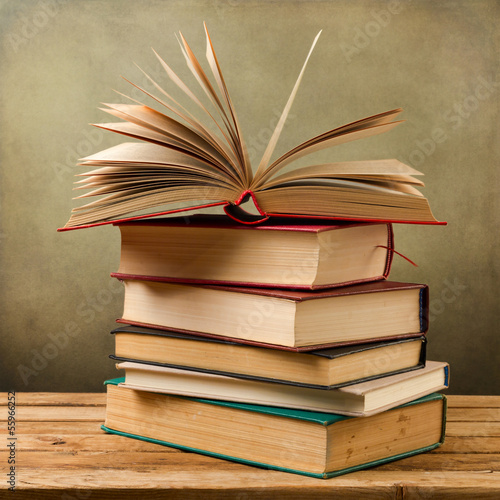 Vintage old books on wooden table over grunge background
